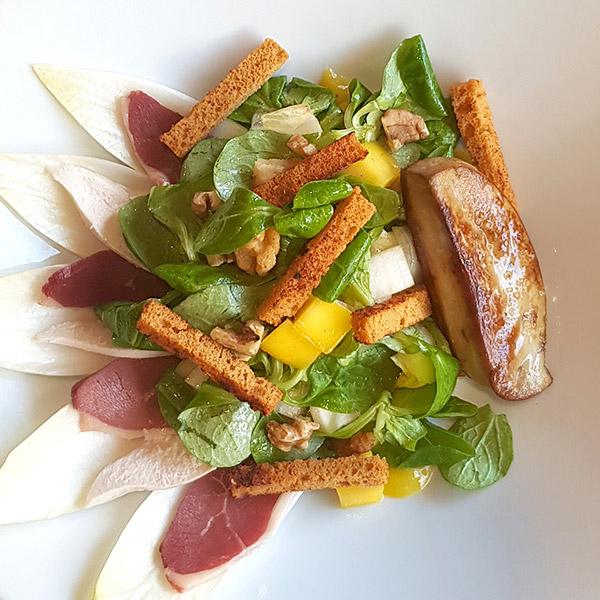 Saalde signature Alain Le Cossec Le PatacrêpeFoie gras poêlé & fleur de sel sur salade de mâche & endive accompagnés de dés de mangue, tranches de magret fumé & lamelles de filet de poulet, croûtons de pain d'épice & cerneaux de noix